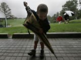 Joseph Nuccio (cq), 3, of Centennial, plays with an umbrella at the 18th green during a rain delay...