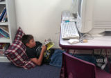 Nate Rino reads under a computer during independent reading in his 5th grade class at  Cheltenham...