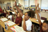 Maxwell Elementary School 5th graders raise their hands to answer a mathematics problem on...