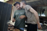SGT Juan Polino, cq, a member of Fort Carson's 3rd ACR, kisses his father Ramon, cq, as he grills...