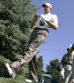 Retief Goosen opens a Granola Bar while heading off the first tee box as players try to keep their...