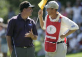 Phil Mickelson loosens up with his caddie Jim Mackay on the ninth gree of his final round at the...
