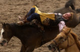 Brandon Holmes, of Eva, AL., holds on tight during the saddle bronc riding event at the Annual...