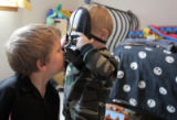 Dakota Givens, cq, left, looks at his brother Carson through a Darth Vader mask on Thursday,...