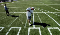 Denver Broncos Football Club's Brett Baird, cq, Assistant Turf Manager, right,  paints a pass rush...