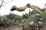 Boulder County equipment operator Dean Rausch, 45, cq, helps direct a back hoe as they try to...