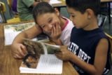 Franchesca Gallegos, 7, and Shaun Esquibel (cq), 7, read a book in their second-grade class. ...