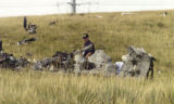 An NTSB Investigator looks over the wreckage of a twin-engine Cessna Sunday morning August 14,...