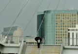 Denver, CO Aug. 16, 2005 A pedestrian crosses the Millennium Bridge, which spans the tracks of the...