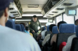 An unidentified immigration agent boards the Limousine Express bus at the first New Mexican check...