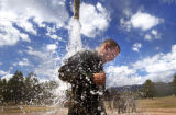 Brett Norris,19, of Naples, Fla.,(cq), a basic cadet in Guts Bravo Company, cools off and cleans...