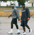 Denver Broncos receiver Rod Smith, left, and linebacker Al Wilson, right, walk in the rain to...