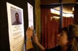 Park employee, Judy Rosen,right, posts missing person signs at the Beaver Meadows Visitor center...