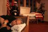 David Stibbs, cq, Avon, sleeps in a pew near the casket of his stepson, Marine Lance Corporal...