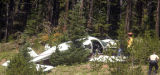Investigators and fire personnel examine a single engine plane  off  the north side of I- 70 at...