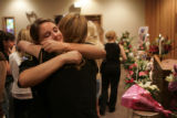 Sarah Lewis, cq, left, hugs Stacy Story during a memorial service for Kris and Lilly Kueneman at...
