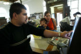 (Denver County, Colo., August 4, 2005) Circulation clerk Ruben Terrones, left, helps Patricia...