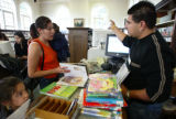 (Denver County, Colo., August 4, 2005) Circulation clerk Ruben Terrones, right, helps Patricia...