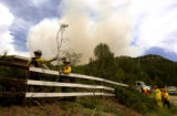 Smoke fills the sky over Wetmore, Colo., as crews clear paths to homes in danger, by cutting down...