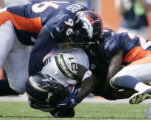 JPM1037-- Denver Broncos defensive tackle Michael Myers, #96, and safety Nick Ferguson, #25, hit...