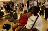 Sandra Williams (cq) ,46,left, of New Orleans, La., gets some much needed rest as Red Cross...