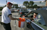 Ryan Dennis, 23, of the Guardian Angels, left, gets a donation from Holly Bosler, right, as...