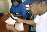 Hurricane Katrina evacuees Lionell Daggs (right, cq) and his wife Betty (cq, left) go over some of...