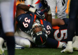 Denver Broncos fullback Kyle Johnson bends over the goal line backwards to score a touchdown in...