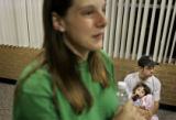 Hurricane Katrina evacuees Scott Richard (cq, right), 23, of Mandeville, La. holds his daughter...