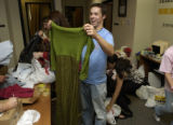 Mike Ross, (cq) junior, holds up a green dress chuckling as he folds it for packing as another...