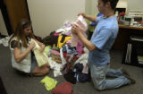 Maggie Jones (cq) left, sophomore,  seated, white vest, folds clothes for packing with Mike Ross,...
