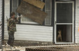 (Lt. to Rt.) Colorado National Guardsman Gerohan Salas, of Lakewood, knock on the window of a home...