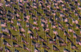 A woman walks through a section of flags September 11, 2005 in the Healing Field at the Mamie Doud...