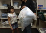 Denise Tran,5, (cq), left of frame, withi her mom, Linh Tran (cq), together hold her bag of newly...