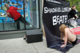 Niketown employee David Banks, cq, leans to get a better view of protester Julie Stephan, cq, at...