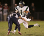 ThunderRidge wide reciever, Eric Moats, right, tries to avoid a hit by Dakota Ridge Kicker, Zak...