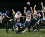 Lyons kicker Sam Fortier, left #14, kicks the game-winning extra point putting Lyons up 21-20 as...