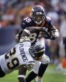 The Denver Broncos' Ashley Lelie (#85, WR) stiff arms the San Diego Chargers' Drayton Florence...