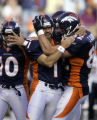 Denver Broncos teammates mob Jason Elam (#1, K) after a field goal in the closing seconds that...