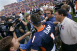 The Denver Broncos' Jason Elam (#1, K) is mobbed by reporters after winning the game with a 41...