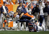 The Denver Broncos' John Lynch (#47, S) and Champ Bailey (#24, CB) combine on the tackle of the...
