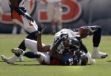 San Diego's Keenan McCardell, top #87, is pulled down by Denver Broncos safty, Nick Ferguson,...