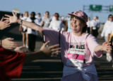 Carolyn Bauer (cq) 56, from Denver is greeted with open arms by volunteers as she finishes a 5K...