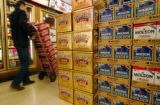 (GOLDEN, Colo., July 21, 2004) A Argonaut Liquors employee carts beer by a display of Extra Gold...