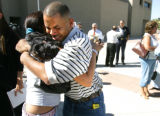 Jose Silva, 25, cq, right, hugs a family friend Sarah Mares, cq,  for comfort after a press...