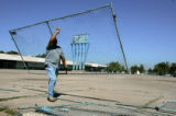 Tom Anderson (cq)  , from American Fencing sets up fence around the ruins of Dahlia Square at east...