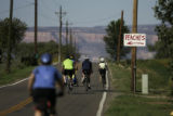 Bicyclists ride past a peach orchard in Palisade, Colorado during a 25-mile ride in the annual...