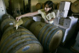 "Enologist Kelly Bradford (cq), pours yeast into wine barrels, (or ""innoculates the..."