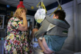 Debbie Miller (cq) uses an electric device to help ger her son Brian Miller (cq) out of his bed...