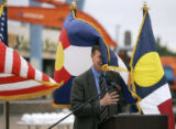 Gusts of wind wrap Denver mayor, John Hickenlooper, in the Colorado State Flag during a press...
